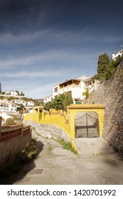 side street down a hill in spain of houses with the city of almunecar in the background