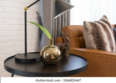 Side table with black table light bedside brown leather sofa in industrial style decoration.