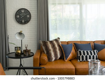 side table lamp and brown leather sofa with pattern cushions in industrial style decoration