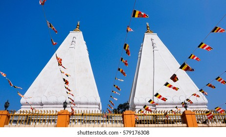 Side temples near Mahabodhi temple with prayer flags in foreground and blue sky in background. At Bodhgaya, India