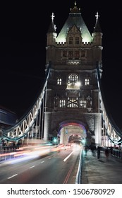 A side of the Tower Bridge of London at night with people walking by and cars captured with long exposure technique