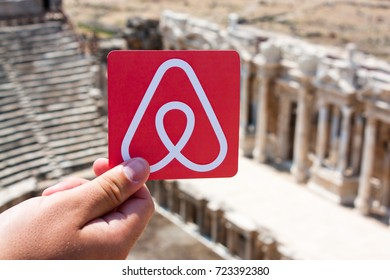 Side, Turkey. August, 2017. Printed on paper logos of the famousbooking service Airbnb. Landscape with old palace are on the background. Concept.