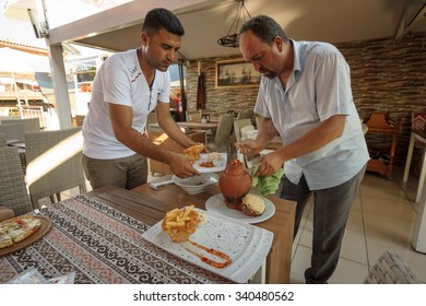 SIDE, TURKEY - JULY 07, 2015: The restaurant in Side, the waiter served the meat from the clay pot.