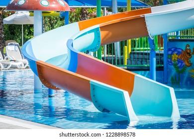 Side, Turkey - June 2018: Curved water slide descending into blue pool for children