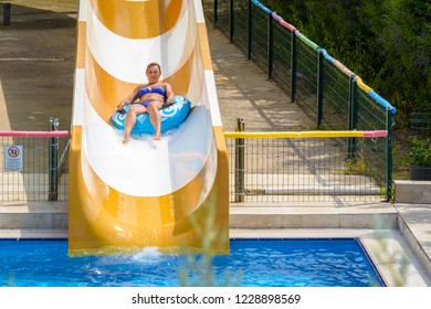 Side, Turkey - June 2018: Woman in swimsuit rolls on tubing on water slide in aquapark