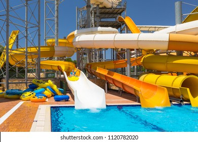 Side, Turkey - June 7, 2018: Dad and little son having fun on waterslide during sun holidays, Turkey. Waterpark at Pegasos World Hotel is a popular tourist destination at Turkish Riviera.