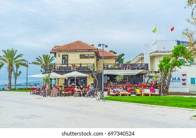 SIDE, TURKEY - MAY 8, 2017: Tourist enjoy their vacations in Mediterranean resort, relax in cozy restaurant, located on the coast in city center, on May 8 in Side.