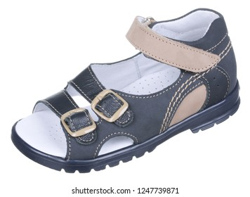 Side upper view of black and beige leather and suede boy sandal with slits and slots, perforated insole, velcro and two clasps, isolated on white