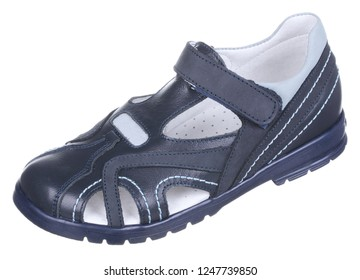 Side upper view of dark blue and gray leather and suede boy sandal with slits and slots, perforated insole and velcro, isolated on white