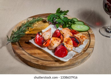 Side upper view on circle wooden cutting board with pieces of baked chicken, grilled paprika, slices of fresh cucumber, red onion, rosemary and wineglass of red wine