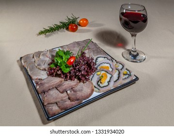 Side upper view on square plate with slices of three types of boiled meat and one of meat roll, greens, rosemary, cherry tomatoes and wineglass of red wine