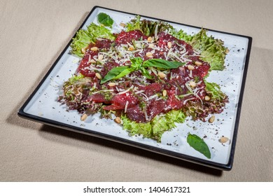 Side upper view on square plate with beef carpaccio decorated with salad leaves, granted cheese, sprig and leaves of mint, peanuts and kitchen herbs