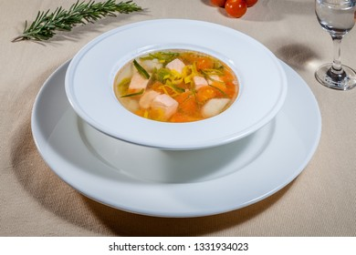 Side upper view on white soup plate on big saucer with transparent bouillon with pieces of different vegetables and meat, rosemary, cherry tomatoes and wineglass of vodka