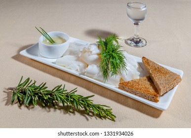 Side upper view on white rectangular plate with slices of lard, sauce, dill, rosemary, toasts of black bread and misted wineglass of cold vodka