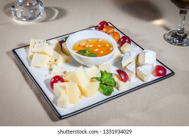 Side upper view on white square plate with pieces of three types of cheese, mint, grape, sunflower oil in sauce boat, candle in glass candlestick and leg of wineglass with red wine