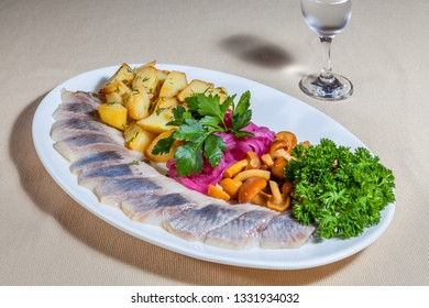 Side upper view on white oval plate with slices of salted herring, fried potato, marinated mushrooms and red onion, greens and misted wineglass of cold vodka