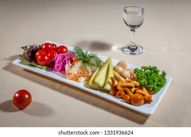 Side upper view on white rectangular plate with different pickles: tomatoes, red onion, cabbage, cucumbers, mushrooms and garlic with addition of greens, cherry tomato and wineglass of vodka