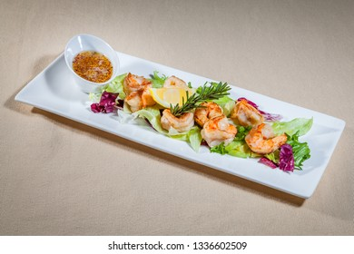 Side upper view on white rectangular plate with shrimp salad consists of: shrimps, greens, rosemary, slice of lemon and oiler with Dijon mustard
