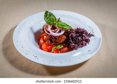 Side upper view on white oval plate with vegetable salad consists of: red cabbage, marinated red onion, greens, mint and other