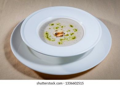 Side upper view on white soup plate with cream soup with green flavoring and slice of champignon mushroom standing on big white saucer