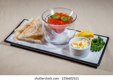 Side upper view on white rectangular plate with different snacks: white toasts, red caviar with mint in trasparent vase, greens, slices of lemon and oiler with butter
