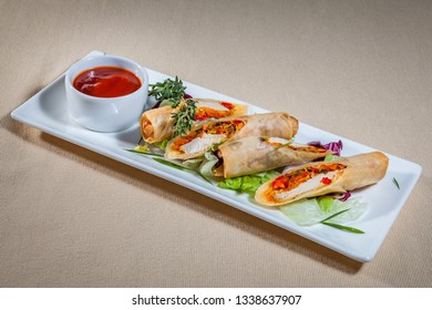 Side upper view on white rectangular plate with pancakes stuffed with meat and vegetable filling and with addition of: greens, rosemary, red cabbage and sauce boat with ketchup