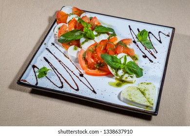 Side upper view on white square plate with slices of mozzarella cheese and tomato flavored with mint, olive oil, soy sauce and kitchen herbs