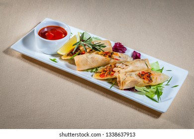 Side upper view on white rectangular plate with pancakes stuffed with meat and vegetable filling and with addition of: greens, rosemary, red cabbage, slice of lemon and sauce boat with ketchup