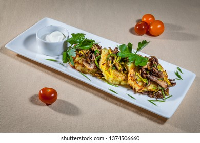 Side upper view on white rectangular plate with circles of mushed potato with grilled honey agaric mushrooms on their tops, white sauce boat with garlic sauce, parsley and cherry tomatoes