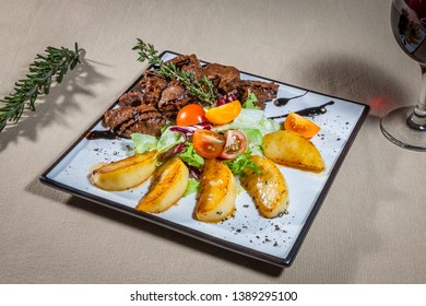 Side upper view on white square plate with slices of fried potato, pieces of stewed bief, greens, cut cherry tomatoes, sprigs of rosemary and wineglass of red wine