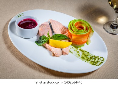 Side upper view on white plate with steamed salmon and lingonberry sauce, decorated with mint, slice of lemon, roll of thin carrot and vegetable marrow and track of green sauce,wineglass of white wine