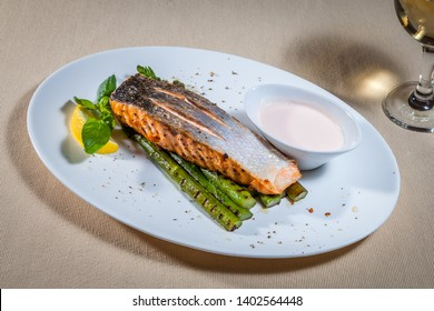Side upper view on white oval plate with grilled salmon on asparagus and garlik sauce, decorated with mint, slice of lemon and kitchen herbs, also wineglass of white wine