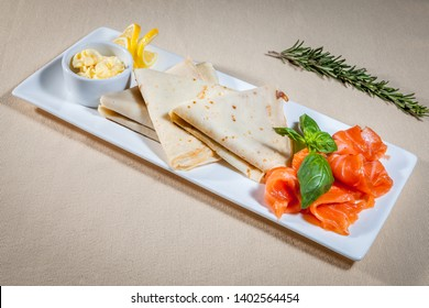 Side upper view on white rectangular plate with triangle pancakes, slices of salted salmon and butter in sauce boat decorated with slices of lemon, mint and sprig of rosemary