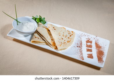 Side upper view on white rectangular plate with pancakes and sour cream in sauce boat decorated with sprig of parsley, leaves of green onion and cinnamon