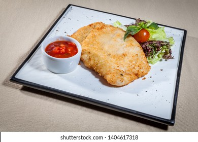 Side upper view on white square plate with pork chop fried in breadcrumbs, few leaves of salad, cherry tomato, sprig of mint and ketchup in sauce boat all decorated with kitchen herbs