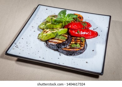 Side upper view on white square plate with slices of grilled vegetables: aubergine, zucchini and paprika, all decorated with green sauce, kitchen herbs and sprig of mint
