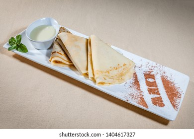 Side upper view on white rectangular plate with pancakes and condensed milk in sauce boat decorated with sprig of mint and cinnamon