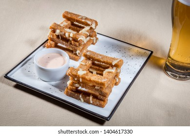 Side upper view on white rectangular plate with toast-sticks of rye bread with melted cheese and garlic sauce in sauce boat decorated with kitchen herbs, also glass of beer