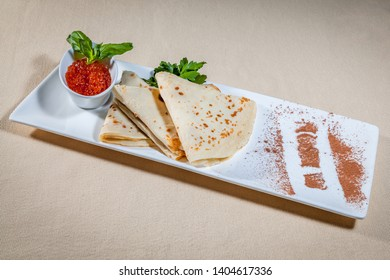 Side upper view on white rectangular plate with pancakes and red caviar in sauce boat decorated with sprigs of mint and parsley, and cinnamon