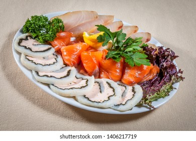 Side upper view on white ellipse plate with three sorts of fish slices: salted salmon and halibut, and fish roll, decorated with slices of lemon, dill and parsley sprigs, and lettuce leaves