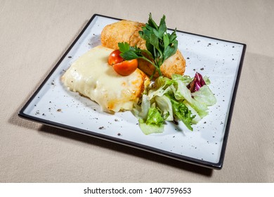Side upper view on white square plate with pork baked under melted cheese, Kiev cutlet in bread scrumbs, decorated with lettuce leaves, sprigs of parsley, cut cherry tomato and kitchen herbs