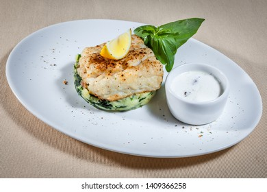Side upper view on white oval plate with baked fish and slice of lemon on baked garnish with tartar sauce in sauce boat, decorated with sprig of mint and kitchen herbs