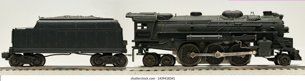 A side view of a 1950's era electric toy train with its decals removed. This steam locomotive was manufactured by Lionel during the Postwar Period.