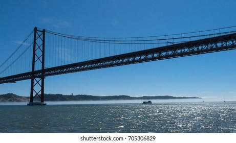 """Side view of the """"25 de Abril"""" Bridge with blue sky and hills in the background, sea and boat underneath it (Lisbon Portugal)"""