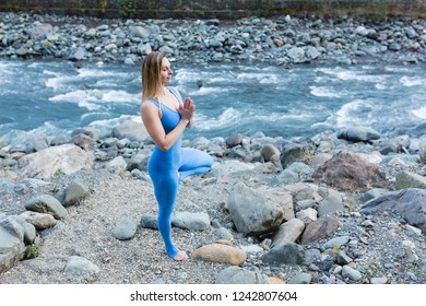 Side view from above - a slim young woman does a yoga pose Vrikshasana and meditates while enjoying the sound of a mountain river on a warm autumn day. Concept of balance and spirituality