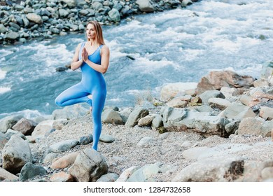 Side view from above - a slim young female does a yoga pose Vrikshasana and meditates while enjoying the sound of a mountain river on a warm autumn day. Concept of balance and spirituality
