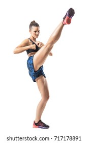 Side view action motion of tough female mma fighter doing high kick. Full body length portrait isolated on white studio background.