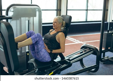 Side view of active senior Caucasian woman exercising with leg press machine in fitness studio. Bright modern gym with fit healthy people working out and training