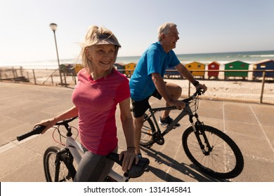 Side view of active senior couple riding a bicycle on a promenade at beach
