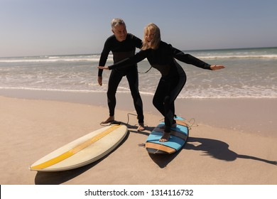 Side view of active senior surfer couple standing with surfboard on the beach